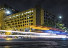FILE - In this Nov. 1, 2017, file photo, traffic along Pennsylvania Avenue in Washington streaks past the Federal Bureau of Investigation headquarters building. Federal policies emphasizing privacy over disclosure and a complex web of government officials could undermine improvements in communication and coordination if another cyberattack on U.S. election systems occurs. (AP Photo/J. David Ake, File)