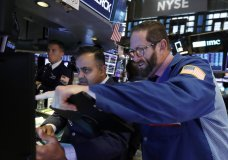 Trader Stephen Gilmartin, right, works with specialist Dilip Patel on the floor of the New York Stock Exchange, Wednesday, Nov. 13, 2019. Stocks are opening slightly lower on Wall Street led by declines in banks and industrial companies. (AP Photo/Richard Drew)