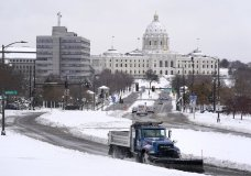 A plow truck makes its way up the hill in front of the Cathedral of St. Paul, with the Capitol building in the backdrop on Wednesday, Nov. 27, 2019, in St. Paul, Minn. (Leila Navidi/Star Tribune via AP)