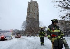 Minneapolis firefighters leave after a deadly fire at a high-rise apartment building, in background, Wednesday, Nov. 27, 2019, in Minneapolis. (David Joles/Star Tribune via AP)
