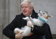 Britain's Prime Minister and Conservative Party leader Boris Johnson holds his dog Dilyn as he leaves after voting in the general election at Methodist Central Hall, Westminster, London, Thursday, Dec. 12, 2019. The general election in Britain on Thursday will bring a new Parliament to power and may lead to a change at the top if Prime Minister Boris Johnson's Conservative Party doesn't fare well with voters. Johnson called the early election in hopes of gaining lawmakers to support his Brexit policy. (AP Photo/Frank Augstein)