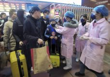 Medical workers use an infrared thermometer to check travelers at a train station in Nanchang in southern China's Jiangxi Province, Wednesday, Jan. 22, 2020. Chinese health authorities urged people in the city of Wuhan to avoid crowds and public gatherings, after warning that a new viral illness that has infected more than 400 people and killed at least nine could spread further. (Chinatopix via AP)