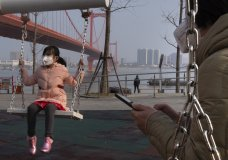 A girl wears a face mask as she play on a swing near the Yingwuzhou Yangtze River Bridge in Wuhan in central China's Hubei Province, Wednesday, Jan. 29, 2020. Countries began evacuating their citizens Wednesday from the Chinese city hardest-hit by a new virus that has now infected more people in China than were sickened in the country by SARS. (AP Photo/Arek Rataj)