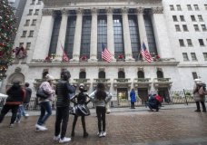 FILE - In this Jan. 3, 2020, file photo visitors to the New York Stock Exchange pause to take photos in New York. The U.S. stock market opens at 9:30 a.m. EST on Wednesday, Jan. 8. (AP Photo/Mary Altaffer, File)