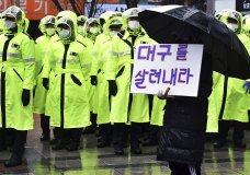 """A protester holds a sign to denounce government's coronavirus responses in Daegu, South Korea, Tuesday, Feb. 25, 2020. China and South Korea on Tuesday reported more cases of a new viral illness that has been concentrated in North Asia but is causing global worry as clusters grow in the Middle East and Europe. The signs read """"Save Daegu.""""(Lee Moo-ryul/Newsis via AP)"""
