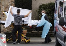 A staff member blocks the view as a person is taken by a stretcher to a waiting ambulance from a nursing facility where more than 50 people are sick and being tested for the COVID-19 virus, Saturday, Feb. 29, 2020, in Kirkland, Wash. Health officials reported two cases of COVID-19 virus connected to the Life Care Center of Kirkland. One is a Life Care worker, a woman in her 40s who is in satisfactory condition at a hospital, and the other is a woman in her 70s and a resident at Life Care who is hospitalized in serious condition. Neither have traveled out of the country. (AP Photo/Elaine Thompson)