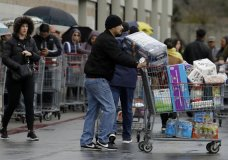 Costco customers roll groceries to their cars as others wait to enter the store on Saturday, March 14, 2020, in San Leandro, Calif. Empty store shelves. Empty churches. Shuttered classrooms and courts. Warnings everywhere to wash hands and avoid close contact. Efforts to stop the spread of the coronavirus in California are affecting virtually every facet of life in the Golden State in ways big and small — and in some cases, surreal. For most people, the new coronavirus causes only mild or moderate symptoms. For some it can cause more severe illness. (AP Photo/Ben Margot)