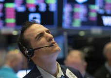 Stock trader Gregory Rowe works at the New York Stock Exchange, Wednesday, March 18, 2020 in New York. Global stock markets have sunk in a third day of wild price swings after President Donald Trump promised to prop up the U.S. economy through the coronavirus outbreak.(AP Photo/Mark Lennihan)