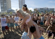 Cece Guida, 19, top, of New York City, pushes on Sam Reddick, 20, of Evansville, Ind., as spring break revelers look on during a game of chicken fight on the beach, Tuesday, March 17, 2020, in Pompano Beach, Fla. As a response to the coronavirus pandemic, Florida Gov. Ron DeSantis ordered all bars be shut down for 30 days beginning at 5 p.m. and many Florida beaches are turning away spring break crowds urging them to engage in social distancing. (AP Photo/Julio Cortez)