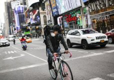 """A bicycle delivery worker wears a protective face mask as he rides through a sparsely populated Times Square due to COVID-19 concerns, Friday, March 20, 2020, in New York. New York Gov. Andrew Cuomo is ordering all workers in non-essential businesses to stay home and banning gatherings statewide. """"Only essential businesses can have workers commuting to the job or on the job,"""" Cuomo said of an executive order he will sign Friday. Nonessential gatherings of individuals of any size or for any reason are canceled or postponed. (AP Photo/John Minchillo)"""