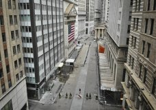 """FILE - In this Saturday, March 21, 2020 file photo, a lone pedestrian wearing a protective mask walks past the New York Stock Exchange as coronavirus concerns empty a typically bustling downtown area in New York. Stocks around the world swung lower Monday, March 23 even after the Federal Reserve announced a tidal wave of support for lending markets, going way beyond the """"bazooka"""" it had already unloaded. (AP Photo/John Minchillo, File)"""