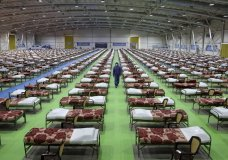 A member of the Iranian army walks past rows of beds at a temporary 2,000-bed hospital for COVID-19 coronavirus patients set up by the army at the international exhibition center in northern Tehran, Iran, on Thursday, March 26, 2020. (AP Photo/Ebrahim Noroozi)