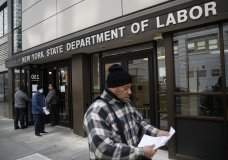 Visitors to the Department of Labor are turned away at the door by personnel due to closures over coronavirus concerns, Wednesday, March 18, 2020, in New York. Applications for jobless benefits are surging in some states as coronavirus concerns shake the U.S. economy. The sharp increase comes as governments have ordered millions of workers, students and shoppers to stay home as a precaution against spreading the virus that causes the COVID-19 disease. (AP Photo/John Minchillo)