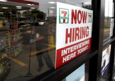 "A sign on the window at a 7-Eleven store reads, ""Now Hiring,"" as an employee inside the store wears a mask and gloves while mopping the floor amid the coronavirus health crisis in Dallas, Wednesday, April 22, 2020. (AP Photo/Tony Gutierrez)"