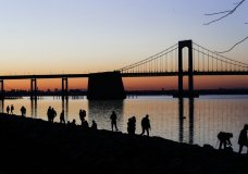 "People gather to watch the sun set behind the Throgs Neck Bridge at LIttle Bay Park Wednesday, April 8, 2020, in the Queens borough of New York. While New York Gov. Andrew Cuomo said New York could be reaching a ""plateau"" in hospitalizations, he warned that gains are dependent on people continuing to practice social distancing. (AP Photo/Frank Franklin II)"