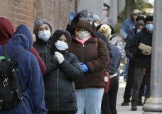 People wear protective masks out of concern for the coronavirus while standing in line outside a pop-up food pantry, Thursday, April 16, 2020, in Chelsea, Mass. (AP Photo/Steven Senne)