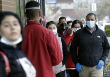 People wear masks as a precaution against the coronavirus as they wait safely distanced in line to enter a supermarket, Monday, April 20, 2020, in Chelsea, Mass. (AP Photo/Steven Senne)