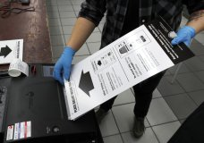 FILE - In this March 17, 2020, file photo a poll worker at the Su Nueva Lavanderia polling place uses rubber gloves as she enters a ballot in the ballot box in Chicago. A new poll from The Associated Press-NORC Center for Public Affairs Research finds Democrats are now much more likely than Republicans to support their state conducting elections exclusively by mail, 47% to 29%. (AP Photo/Charles Rex Arbogast, File)