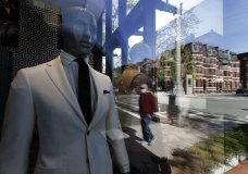 A passer-by wearing a mask out of concern for the COVID-19 coronavirus, background center, walks past mannequins in a clothing store, Wednesday, April 29, 2020, in Boston. Job cuts have escalated across the U.S. economy in recent days that remains all but shut down due measures taken to halt the spread of the virus. (AP Photo/Steven Senne)
