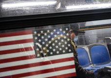 A customer wears personal protective equipment while riding an MTA bus as it operates without fees, Friday, April 24, 2020, in the Bronx borough of New York. (AP Photo/John Minchillo)