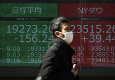 A man wearing a mask to help stop the spread of the new coronavirus walks past an electronic stock board showing Japan's Nikkei 225 and New York Dow indexes at a securities firm in Tokyo Friday, April 24, 2020. Asian shares are lower Friday after an early rally on Wall Street suddenly vanished, the latest example of how fragile the hopes underpinning the stock market's monthlong recovery are.(AP Photo/Eugene Hoshiko)
