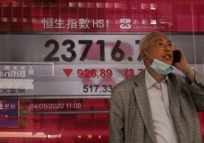 A man wearing face mask walks past a bank electronic board showing the Hong Kong share index at Hong Kong Stock Exchange Monday, May 4, 2020. Shares have skidded in Asia as tensions between the Trump administration and China over the origins and handling of the coronavirus pandemic rattle investors. (AP Photo/Vincent Yu)