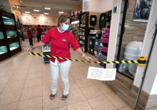 Store manager Natalie Hijazi temporarily closes off the entrance to a Pet Fair store inside The Woodlands Mall to help meet the current occupancy limits in place Tuesday, May 5, 2020, in The Woodlands, Texas. The mall reopened Tuesday with increased health and safety measures in place.Texas' stay-at-home orders due to the COVID-19 pandemic have expired and Texas Gov. Greg Abbott has eased restrictions on many businesses that have now opened. (AP Photo/David J. Phillip)