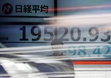 A man stands near an electronic stock board showing Japan's Nikkei 225 index at a securities firm in Tokyo Thursday, May 7, 2020. Asian shares were mixed Thursday after a decline on Wall Street after more depressing data rolled in on the devastation sweeping the global economy. (AP Photo/Eugene Hoshiko)