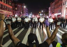 Protesters take a knee on Flatbush Avenue in front of New York City police officers during a solidarity rally for George Floyd, Thursday, June 4, 2020, in the Brooklyn borough of New York. Floyd died after being restrained by Minneapolis police officers on May 25. (AP Photo/Frank Franklin II)