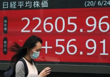 A woman walks past an electronic stock board showing Japan's Nikkei 225 index at a securities firm in Tokyo Wednesday, June 24, 2020. Asian shares were mostly higher on Wednesday with another mood boost from Wall Street, but fears persist over the surge in coronavirus cases in parts of the world. (AP Photo/Eugene Hoshiko)