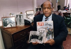 Congressman John Lewis poses in his Atlanta office with two of his favorite items from his collection of memorabilia from his younger days as a civil rights activist in the 1960s. He is holding a Life Magazine cover picturing the famous Selma march in 1965. (He is in this photo at front of the line of marchers.) He is also holding a photo of the 'Big Six' civil rights leaders of the time to plan for the famous March on Washington. The men in the photo are L to R: John Lewis, Whitney Young, A. Phillip Randolph, Martin Luther King, James Farmer, and Roy Wilkins. In background photos (picture at left) of Dr. Martin Luther King with Fred Shuttlesworth and Ralph Abernathy and Lewis with Robert Kennedy (picture at right). (Kimberly Smith/Atlanta Journal-Constitution via AP)