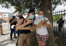 Edif Madrid, right, and Rosa Guillen wait in a line for COVID-19 testing at a mobile testing site in New Orleans, Wednesday, July 8, 2020. Testing sites in New Orleans have been running out of their daily allocation of tests within minutes of opening. (AP Photo/Gerald Herbert)
