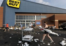 Volunteers help clean up the parking lot outside a Best Buy store, Monday, Aug. 10, 2020, after vandals struck overnight in the Lincoln Park neighborhood in Chicago. Chicago's police commissioner says more than 100 people were arrested following a night of looting and unrest that left several officers injured and caused damage in the city's upscale Magnificent Mile shopping district and other parts of the city. (AP Photo/Charles Rex Arbogast)