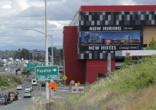"FILE - In this July 9, 2020, file photo, a large video display reads ""Now hiring for our new hotel coming soon!,"" at the new Emerald Queen Casino, which is open, and owned by the Puyallup Tribe of Indians, in Tacoma, Wash. The United States added 1.8 million jobs in July, a pullback from the gains of May and June and evidence that the resurgent coronavirus has weakened hiring and the economic rebound. (AP Photo/Ted S. Warren, File)"