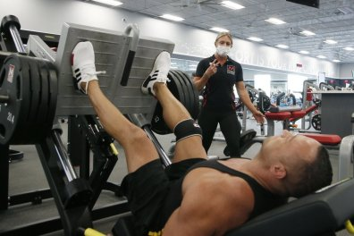 FILE - A trainer and club member at Mountainside Fitness, Thursday, July 2, 2020, in Phoenix, which has challenged Gov. Doug Ducey's gym shutdown order. A judge heard arguments Monday, Aug. 3, 2020, in the challenge filed by Mountainside Fitness and another health club chain. (AP Photo/Ross D. Franklin, File)