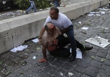 Lebanese man helps an injured man who was wounded by an explosion that hit the seaport, in Beirut Lebanon, Tuesday, Aug. 4, 2020. (AP Photo/Hussein Malla)