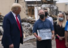 CORRECTS TO SAY THAT JOHN RODE IS NOT THE CURRENT OWNER OF RODE'S CAMERA SHOP; HE IS THE FORMER OWNER - President Donald Trump talks with John Rode, the former owner of Rode's Camera Shop, as he speaks with business owners Tuesday, Sept. 1, 2020, during a tour of an area damaged during demonstrations after a police officer shot Jacob Blake in Kenosha, Wis. (AP Photo/Evan Vucci)