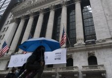 A woman with an umbrella passes the New York Stock Exchange, Monday, Oct. 26, 2020. U.S. stocks are drifting Tuesday, Oct. 27, 2020, as momentum slows a day after Wall Street slumped to its worst loss in a month on worries about rising virus counts and Washington's inability to deliver more aid to the economy. The (AP Photo/Mark Lennihan)