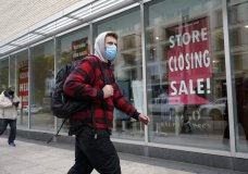 A passer-by walks past a store closing sign, right, in the window of a department store, Tuesday, Oct. 27, 2020, in Boston. Americans may feel whiplashed by a report Thursday, Oct. 29, on the economy's growth this summer, when an explosive rebound followed an epic collapse. The government will likely estimate that the economy grew faster on an annualized basis last quarter than in any such period since record-keeping began in 1947.(AP Photo/Steven Senne)