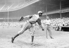 "FILE - In this Aug. 2, 1942, file photo, Kansas City Monarchs pitcher Leroy Satchel Paige warms up at New York's Yankee Stadium before a Negro League game between the Monarchs and the New York Cuban Stars. Major League Baseball has reclassified the Negro Leagues as a major league and will count the statistics and records of its 3,400 players as part of its history. The league said Wednesday, Dec. 16, 2020, it was ""correcting a longtime oversight in the game's history"" by elevating the Negro Leagues on the centennial of its founding. (AP Photo/Matty Zimmerman, File)"