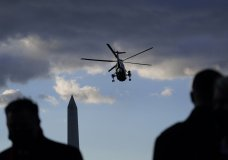 People watch as Marine One with President Donald Trump on board departs on the South Lawn of the White House, Wednesday, Jan. 20, 2021, in Washington. Trump is en route to his Mar-a-Lago Florida Resort. (AP Photo/Alex Brandon)