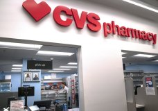 FILE - In this March 17, 2020, file photo, Pharmacist Evelyn Kim, wears a mask and gloves at the CVS pharmacy at Target in the Tenleytown area of Washington. The Biden administration will begin providing COVID-19 vaccines to U.S. pharmacies, including CVS, part of its plan to ramp up vaccinations as new and potentially more serious virus strains are starting to appear. (AP Photo/Carolyn Kaster)