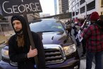 A unidentified protester holds a sign as he blocks a truck on a street next to the Hennepin County Government Center as protesters held vehicles at bay until they honked their horns Monday, March 29, 2021, in Minneapolis. The trial for former Minneapolis police officer Derek Chauvin began with opening statements from both sides. Chauvin is charged with murder in the death of George Floyd during an arrest last May in Minneapolis. (AP Photo/Jim Mone)
