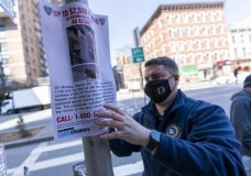 A police officer hangs a sign offering a reward for information on the person who attacked an Asian American woman near the crime scene, Tuesday, March 30, 2021, in New York. The New York City Police Department says an Asian American woman was attacked by a man Monday afternoon who repeatedly kicked her in front of witnesses who seemingly stood by. (AP Photo/Mary Altaffer)