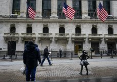 FILE - In this Feb. 16, 2021 file photo, pedestrians pass the New York Stock Exchange in New York. Stocks are off to a mixed start on Wall Street as gains for banks are offset by losses in technology companies and other parts of the market. The S&P 500 was down 0.2% after the first few minutes of trading Wednesday, March 3. (AP Photo/Frank Franklin II, File)