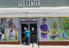 FILE - In this May 7, 2020, file photo, a person looks inside the closed doors of the Pasadena Community Job Center in Pasadena, Calif., during the coronavirus outbreak. While most Americans have weathered the pandemic financially, about 38 million say they are worse off now than before the outbreak began in the U.S. According to a new poll from Impact Genome and The Associated Press-NORC Center for Public Affairs Research 55% of Americans say their financial circumstances are about the same now as a year ago, and 30% say their finances have improved. (AP Photo/Damian Dovarganes, File)
