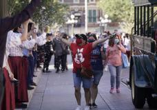 Guests walk down Main Street USA at Disneyland in Anaheim, Calif., Friday, April 30, 2021. The iconic theme park in Southern California that was closed under the state's strict virus rules swung open its gates Friday and some visitors came in cheering and screaming with happiness. (AP Photo/Jae Hong)