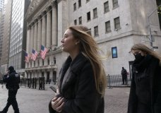 FILE - In this Jan. 13, 2021 file photo, people walk by the New York Stock Exchange. Stocks are opening higher on Wall Street as traders welcome some strong reports on the economy including a drop in jobless claims and a big increase in retail spending, as well as more robust earnings from big companies including Citigroup and United Healthcare (AP Photo/Mark Lennihan, File)