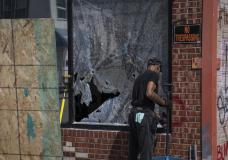 A man cleans up a broken window to a barber shop after shots were fired in George Floyd Square on the one year anniversary of George Floyd's death on Tuesday, May 25, 2021, in Minneapolis. The intersection where George Floyd died was disrupted by gunfire Tuesday, just hours before it was to be the site of a family-friendly street festival marking the anniversary of his death at the hands of police.(AP Photo/Christian Monterrosa)