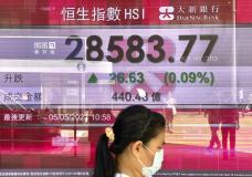 A woman walks past a bank's electronic board showing the Hong Kong share index at Hong Kong Stock Exchange in Hong Kong Wednesday, May 5, 2021. Major Asian stock markets advanced Wednesday after Wall Street fell, while Chinese and Japanese markets were closed for holidays. (AP Photo/Vincent Yu)